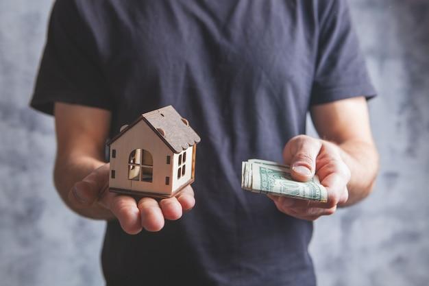 Homem segurando uma casa e dinheiro em um cinza