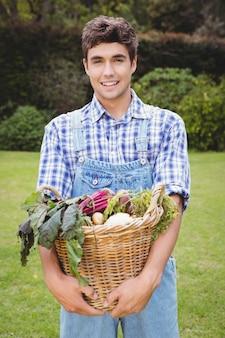 Homem segurando uma cesta de legumes recém-colhidos no jardim