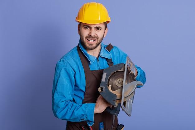 Homem segurando uma circular nas mãos, com expressão facial de raiva, homem barbudo e trabalhador usando avental e capacete protetor amarelo
