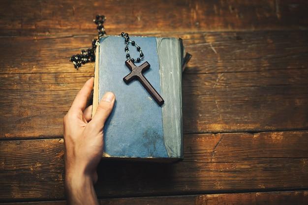 Homem segurando uma cruz e a bíblia