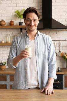 Homem segurando uma dose média de suco de leite