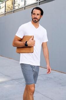 Homem segurando uma embreagem andando na cidade