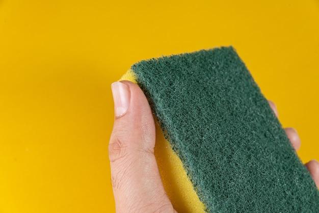 Homem segurando uma esponja de cozinha na mesa amarela