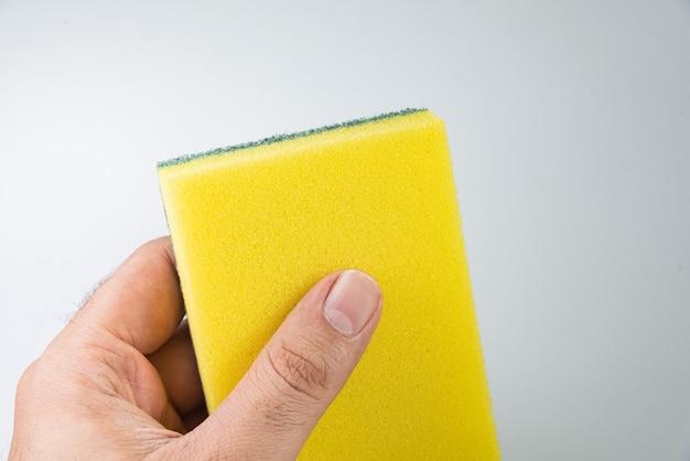Homem segurando uma esponja de cozinha na mesa branca