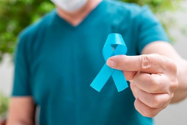 Homem segurando uma fita azul. novembro azul. mês de prevenção do câncer de próstata. a saúde dos homens.