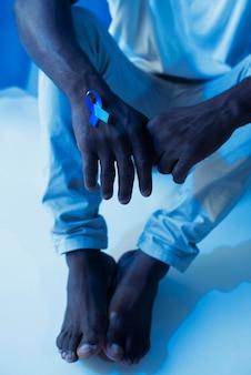 Homem segurando uma fita azul