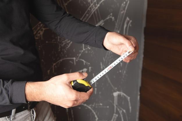 Homem segurando uma fita métrica para construção