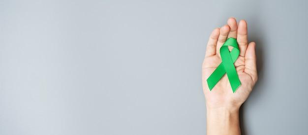 Homem segurando uma fita verde para apoiar as pessoas que vivem e doenças.