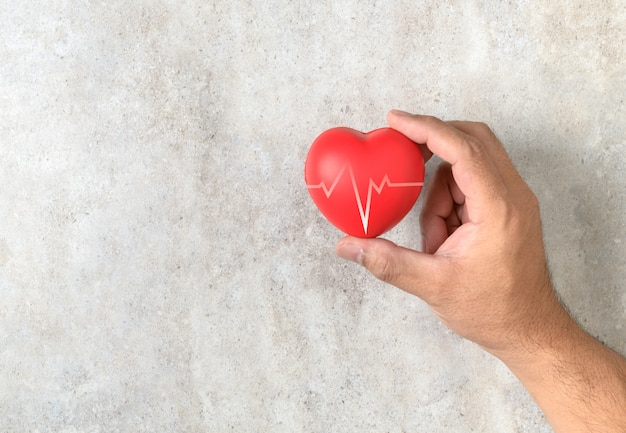 Homem segurando uma forma de coração vermelho na mesa de mármore