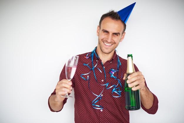 Homem segurando uma garrafa e uma taça de champanhe