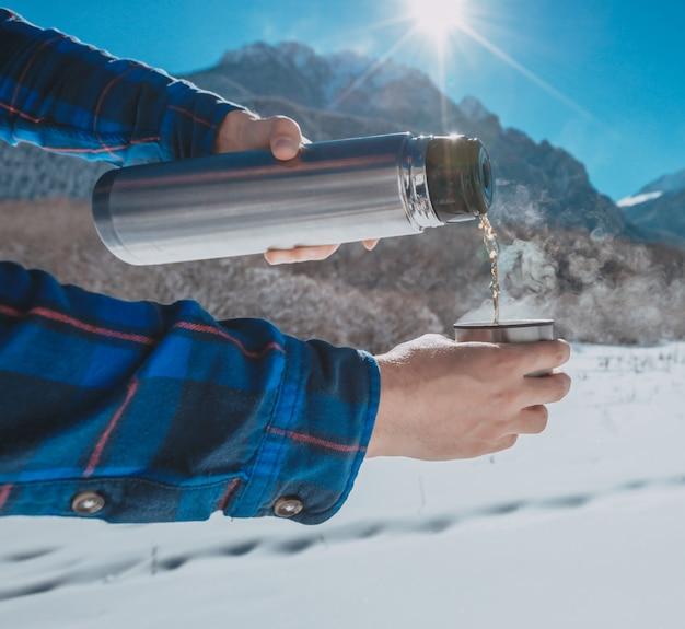 Homem segurando uma garrafa térmica em uma montanha de neve