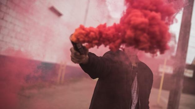 Homem segurando uma granada de fumaça vermelha