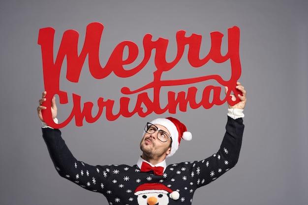 Homem segurando uma grande placa dizendo feliz natal