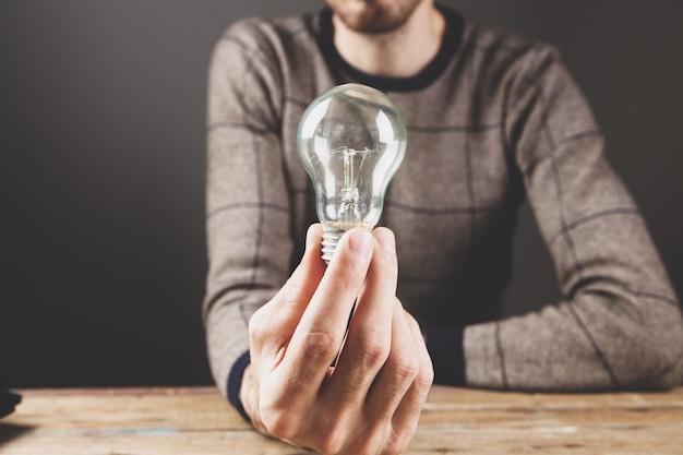 Homem segurando uma lâmpada. ideia de conceito