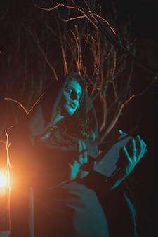 Homem segurando uma lanterna e um livro no meio da noite