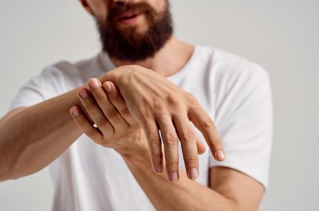 Homem segurando uma lesão na mão, dor, problema de saúde