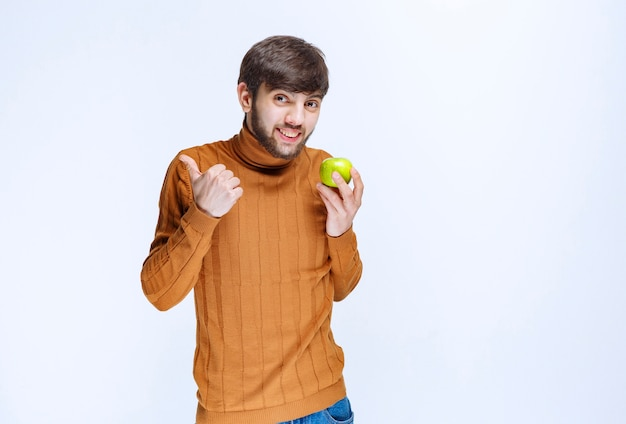Homem segurando uma maçã verde e aparecendo o polegar.