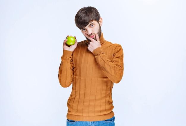 Homem segurando uma maçã verde e pensando.