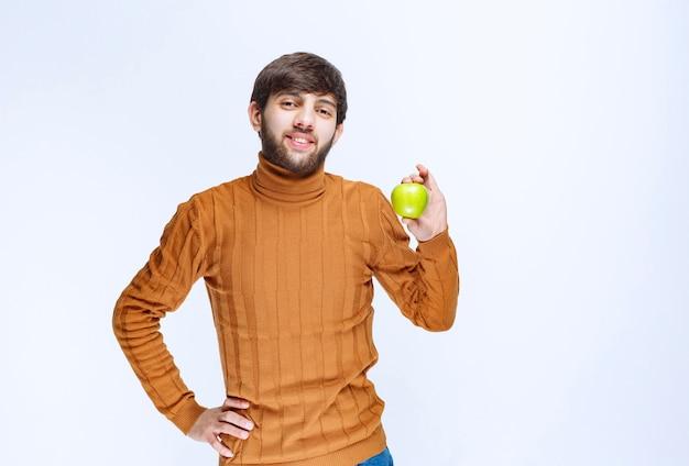 Homem segurando uma maçã verde e promovendo-a aos clientes.