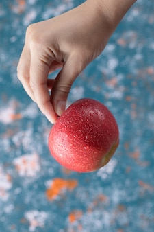 Homem segurando uma maçã vermelha na mão