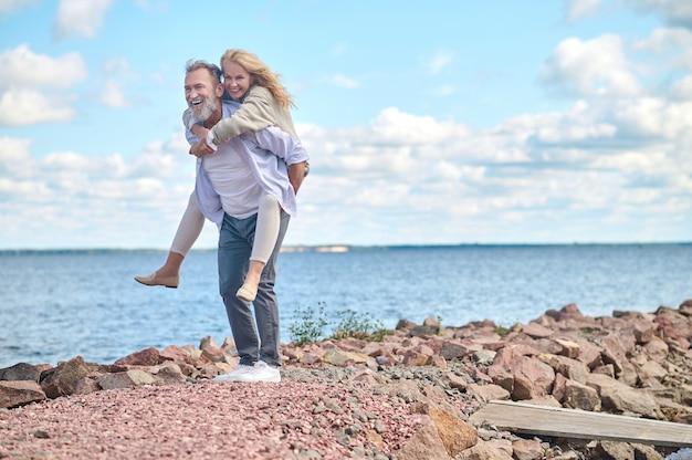 Homem segurando uma mulher sorridente nas costas