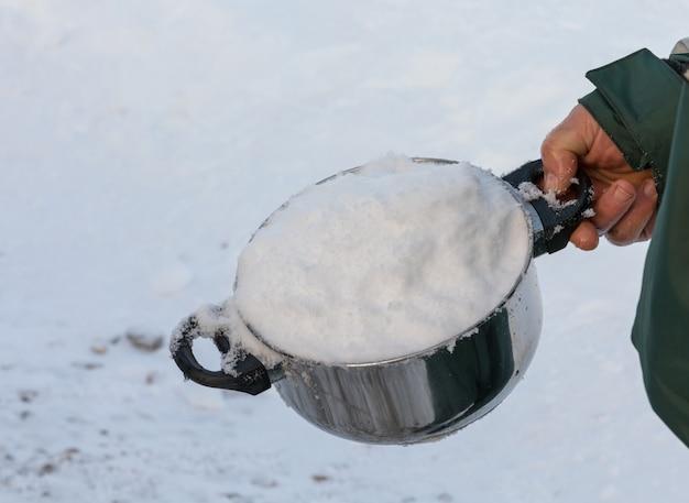 Homem segurando uma panela cheia de neve, por derreter na água potável.
