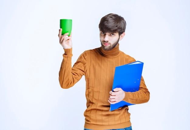 Homem segurando uma pasta azul e um copo verde de bebida.