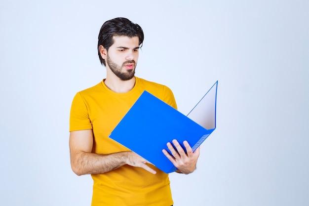 Homem segurando uma pasta azul e verificando os relatórios.