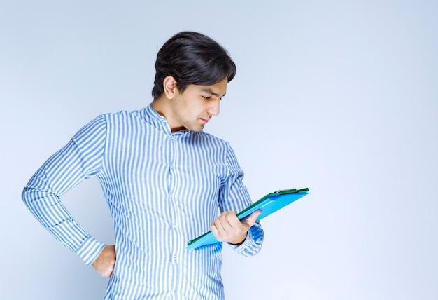 Homem segurando uma pasta de relatório verde e pensando. foto de alta qualidade