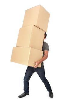 Homem segurando uma pilha pesada de caixas de papelão
