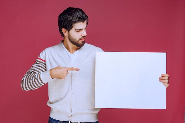 Homem segurando uma placa de ideia em branco e apontando para ela para chamar a atenção.