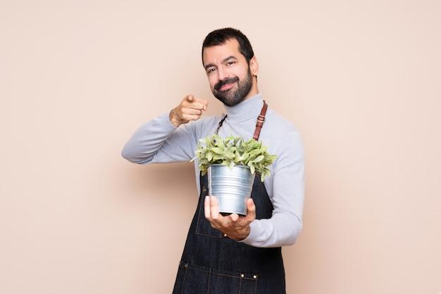 Homem segurando uma planta aponta o dedo para você enquanto sorrindo