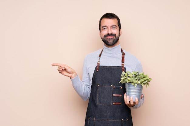 Homem segurando uma planta apontando o dedo para o lado