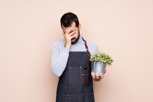 Homem segurando uma planta com expressão cansada e doente