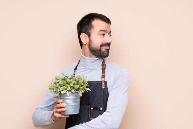 Homem segurando uma planta com os braços cruzados e feliz