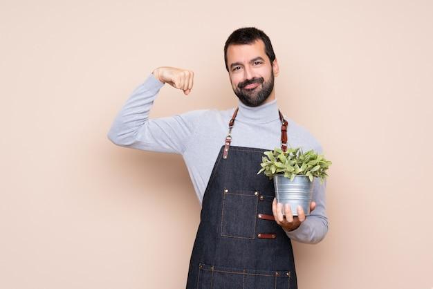 Homem segurando uma planta fazendo forte gesto