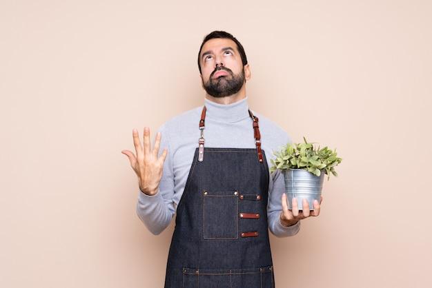 Homem segurando uma planta frustrada por uma situação ruim