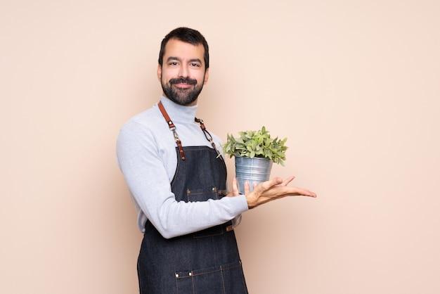 Homem segurando uma planta isolada apresentando uma idéia enquanto olha sorrindo para