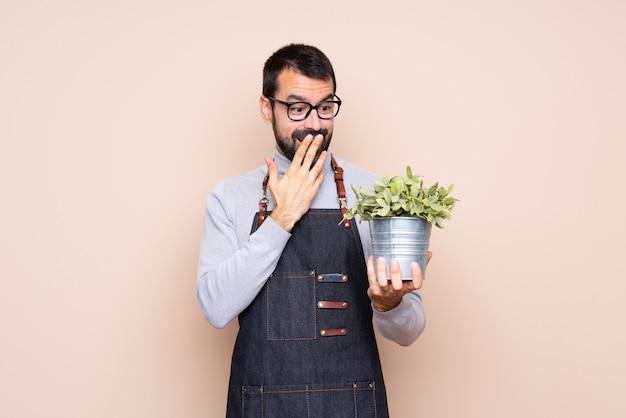 Homem segurando uma planta isolada com óculos e surpreso