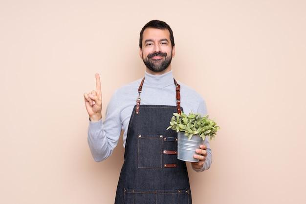 Homem segurando uma planta mostrando e levantando um dedo em sinal dos melhores
