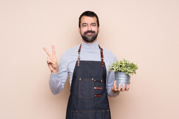 Homem segurando uma planta mostrando sinal de vitória com as duas mãos