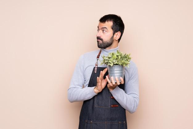 Homem segurando uma planta planejando algo