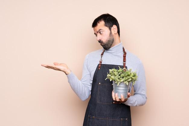 Homem segurando uma planta segurando copyspace com dúvidas