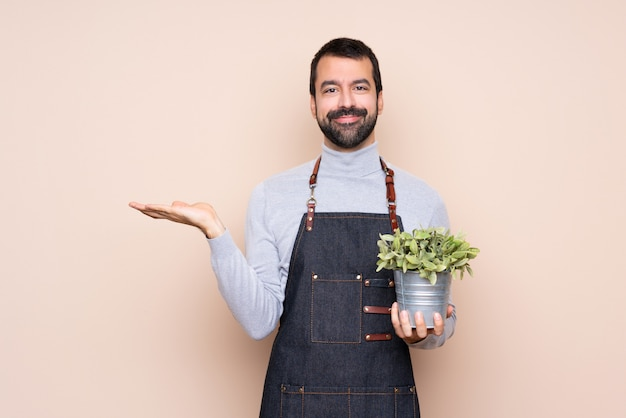 Homem segurando uma planta segurando copyspace imaginário na palma da mão para inserir um anúncio