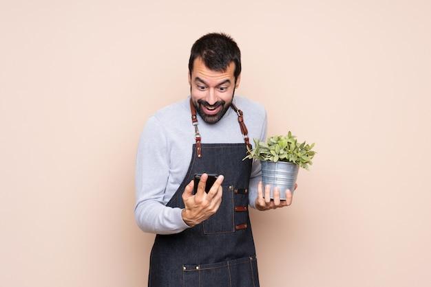 Homem segurando uma planta surpreso e enviando uma mensagem