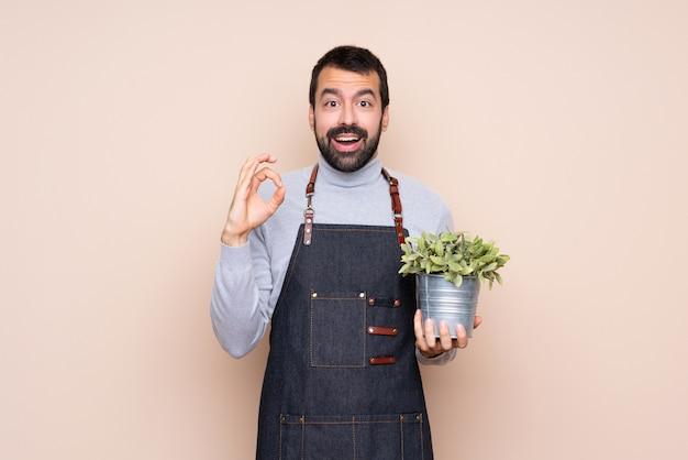 Homem segurando uma planta surpreso e mostrando sinal ok
