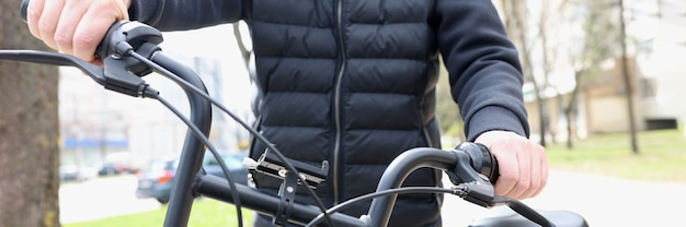 Homem segurando uma roda de bicicleta, close-up ao ar livre