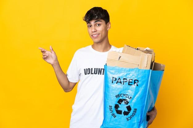 Homem segurando uma sacola cheia de papel para reciclar, sobre o dedo amarelo isolado apontando para o lado