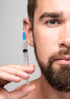 Homem segurando uma seringa ao lado do close-up do rosto