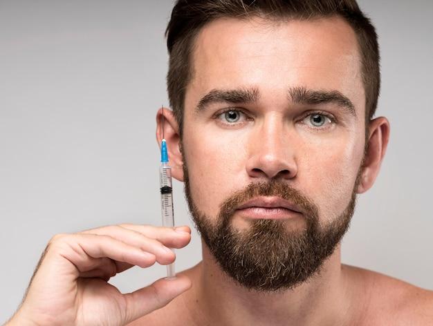 Homem segurando uma seringa perto do rosto